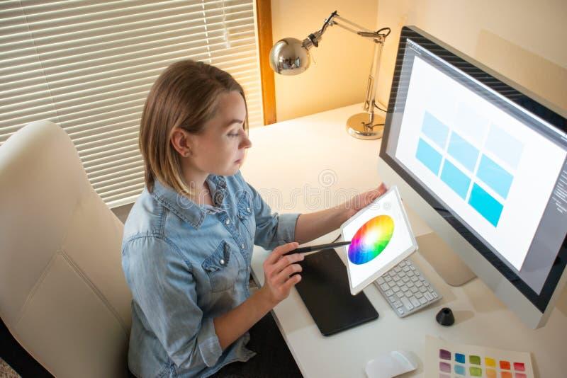 Den grafiska formgivaren arbetar på en dator genom att använda en grafisk minnestavla på en tabell arbeta med rengöringsdukdesign fotografering för bildbyråer