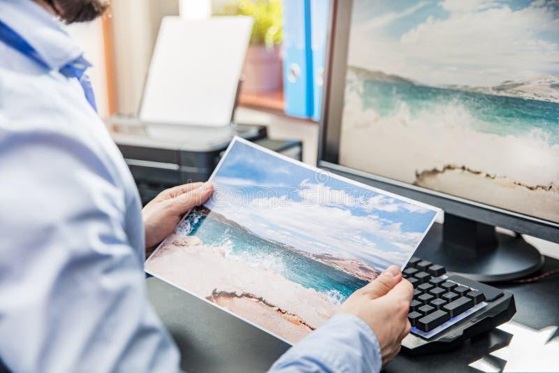 Den grafiska formgivaren jämför det utskrivavna fotoet royaltyfri fotografi
