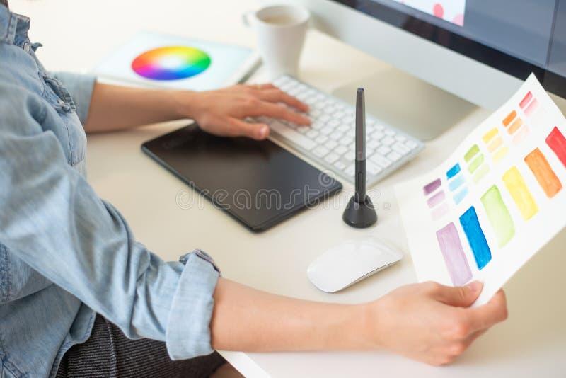 Den grafiska rengöringsdukformgivaren gör arbetet genom att använda en diagramminnestavla, skrivbord arkivfoto