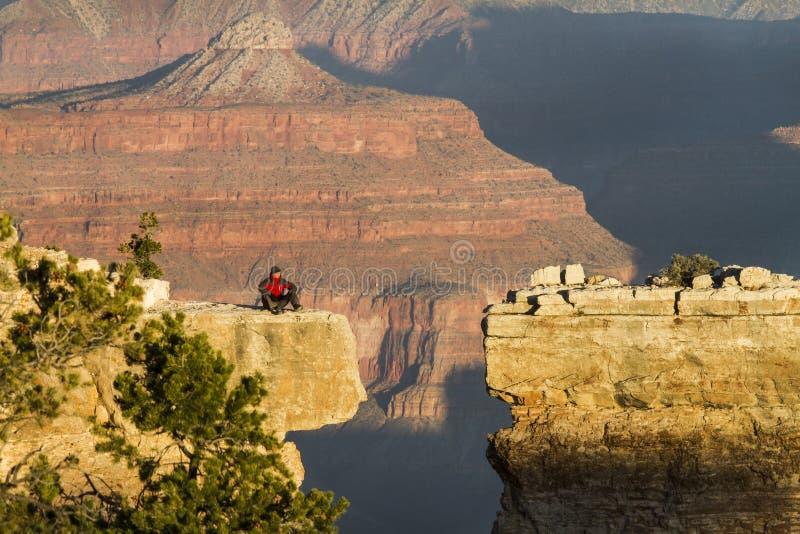 Den Grand Canyon turisten sitter på en avsats på soluppgång arkivbilder