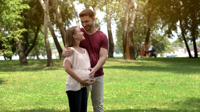 Den gravida familjen som poserar på kamera i, parkerar, lyckligt moderskap och före födseln omsorg royaltyfria bilder