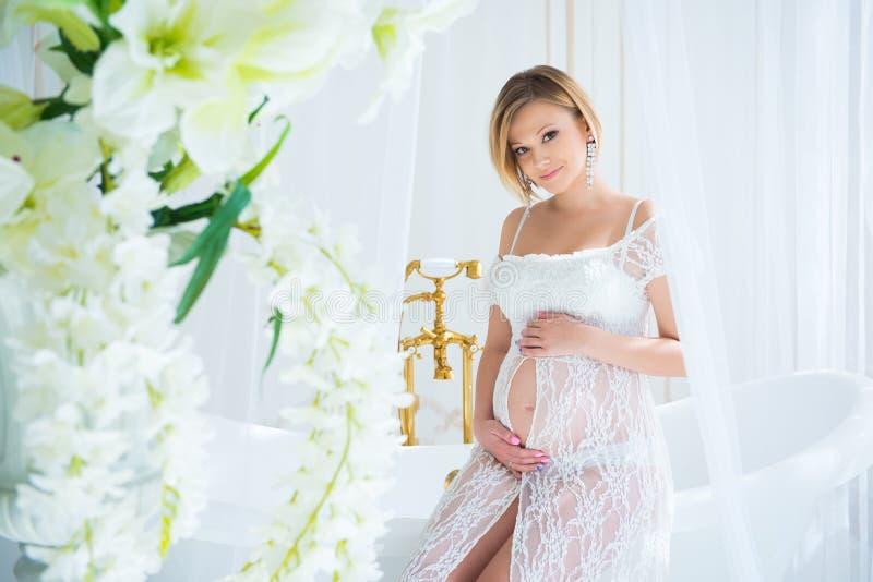 Den gravida flickan i en vit snör åt klänningsammanträde i inre med blommor, och kramar buktar arkivbilder