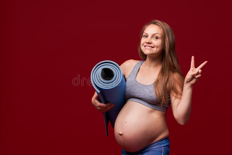 Den gravida flickan rymma sportar som är matta i hennes händer, visar en gest av segern positiv le kvinna i gravid sportkläder royaltyfri bild