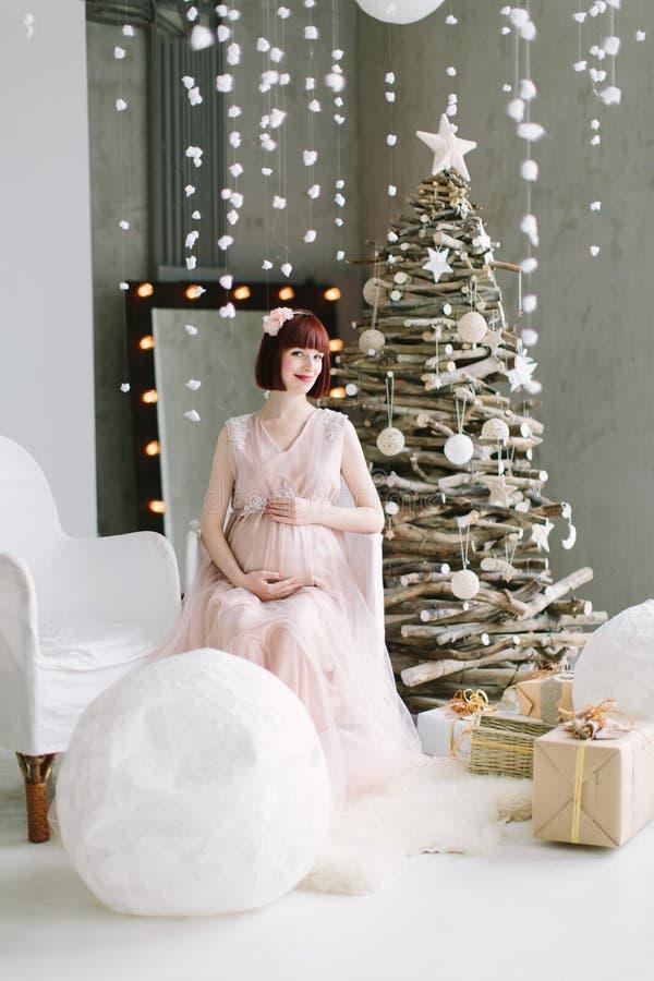 Den gravida flickan sitter på vit stol på vinterbeckground med julträdet arkivfoto