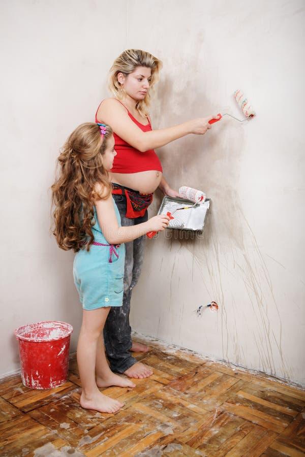 Den gravida modern och hennes lilla dotter reparerar i lägenheten royaltyfria foton