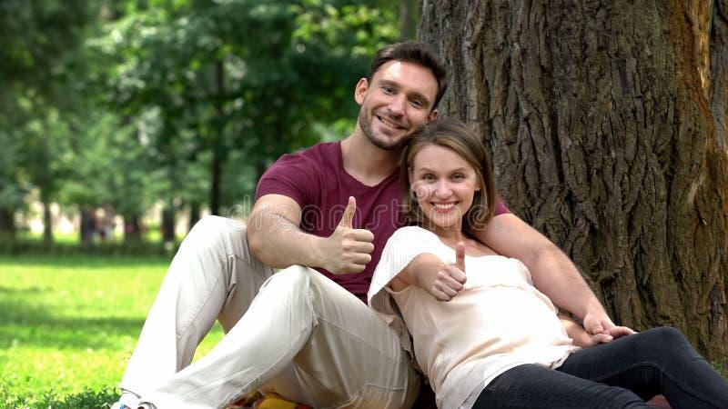 Den gravida parvisningen tummar upp, social service för unga familjer, välfärd royaltyfria foton