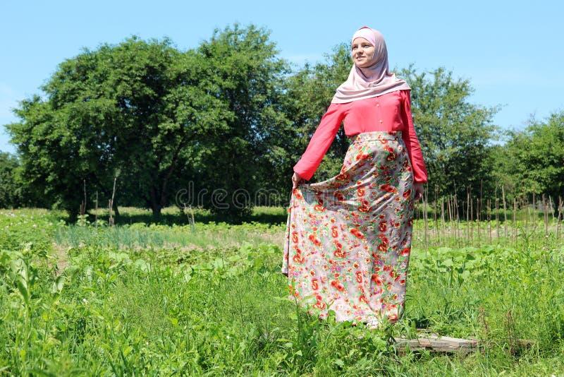 Den gravida unga kvinnan i färgrik muslim kläder poserar framme av kamera i natur royaltyfri foto