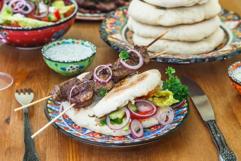 Den grekiska souvlakien tjänade som i en traditionell väg, på pitabröd med den lökcirklar och citronen arkivfoto