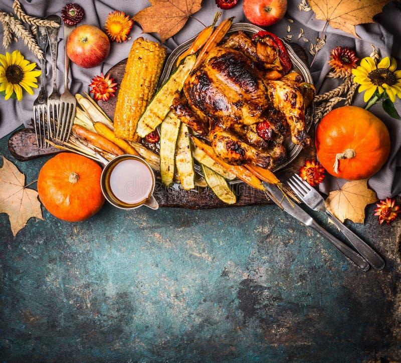 Den grillad välfylld hel kalkon eller höna med organiska skördgrönsaker, pumpa och havreöron för tacksägelsematställe tjänade som arkivbilder