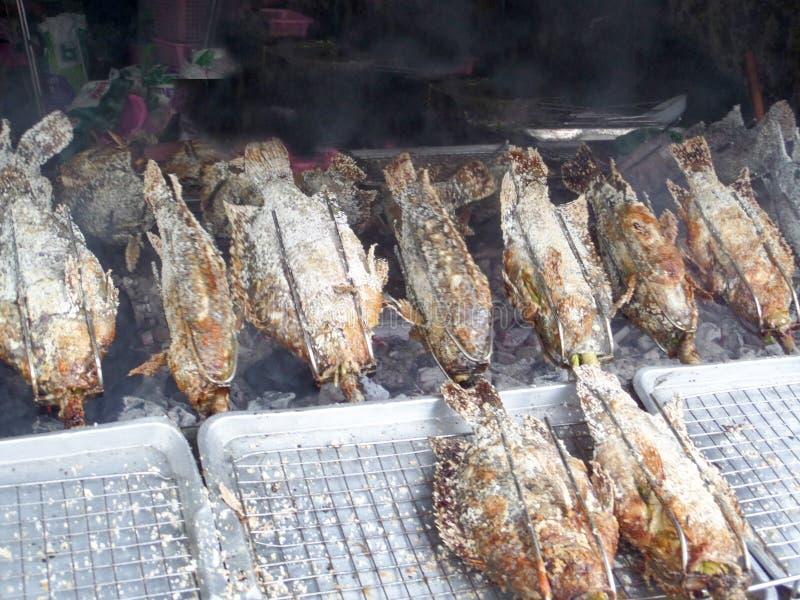 den grillade fisken och saltar och ingrediensörtmatlagning vid rullmachin arkivfoton