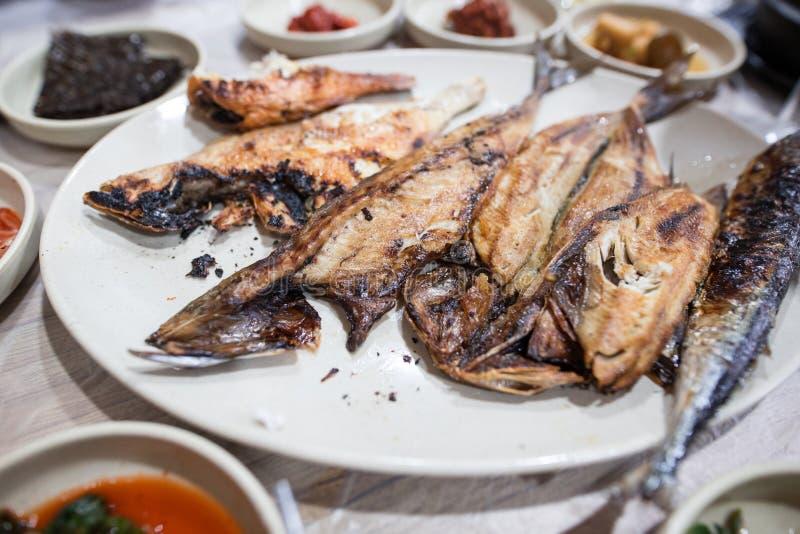 Den grillade fisken tjänade som i den vita maträtten under matställetid fotografering för bildbyråer