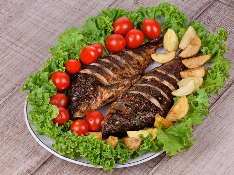 Den grillade fiskkarpen tjänade som med potatisar, tomater körsbär och sallad arkivbild