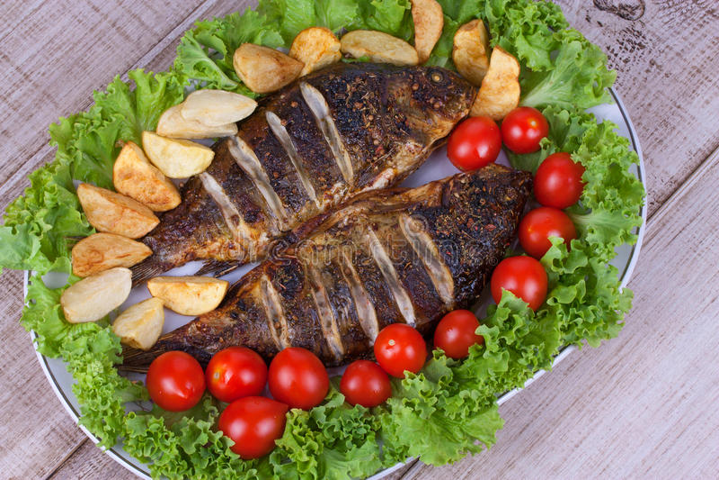 Den grillade fiskkarpen tjänade som med potatisar, tomater och sallad arkivfoton
