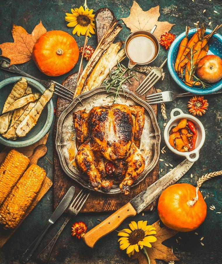Den grillade hela välfyllda höna eller kalkon för tacksägelsedag som tjänas som med sås, pumpor, havre och hösten, skördar grönsa royaltyfria foton
