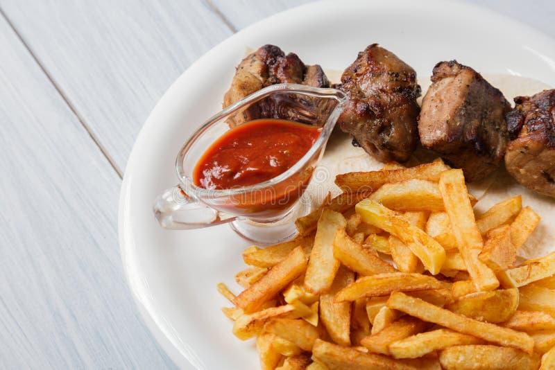 Den grillade kebaben tjänade som med franska småfiskar och sås på trätabellen Slut upp med den selektiva fokusen royaltyfri fotografi