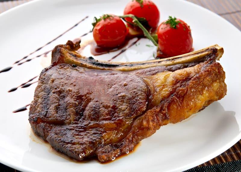den grillade meatplattan ribs vita tomater royaltyfri fotografi