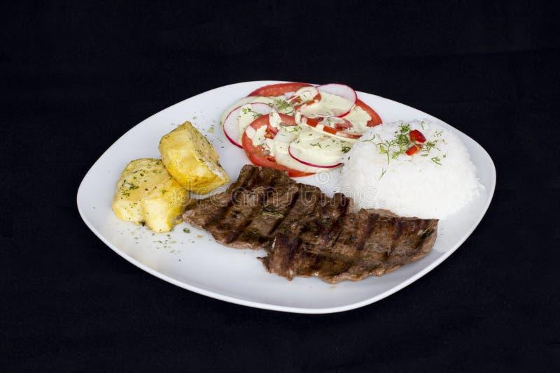 Den grillade nötköttfilén sorterade peruansk maträttchilisås, ris, potatisar, tomater royaltyfri fotografi