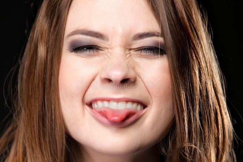 Grimacing. Den unga kvinnadanandedumbommen vänder mot. royaltyfria foton