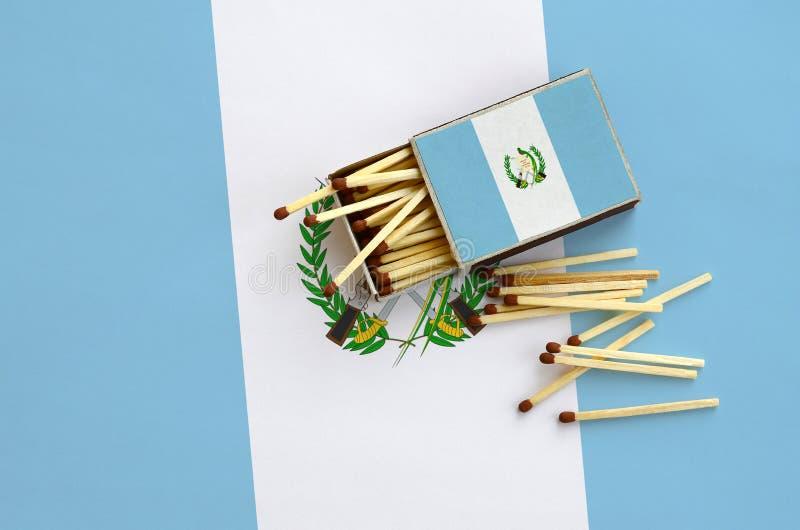 Den Guatemala flaggan visas på en öppen tändsticksask, som flera matcher faller från och lögner på en stor flagga arkivfoto