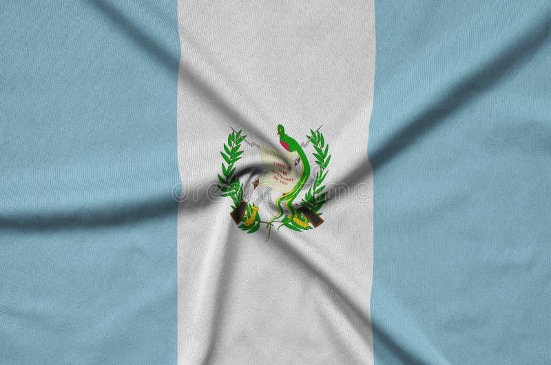 Den Guatemala flaggan visas på ett sporttorkduketyg med många veck Baner för sportlag royaltyfri foto