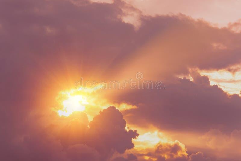 Den gudomliga varma ljusa solnedgången från himlen klyver strålarna av ett mörkt moln royaltyfri fotografi