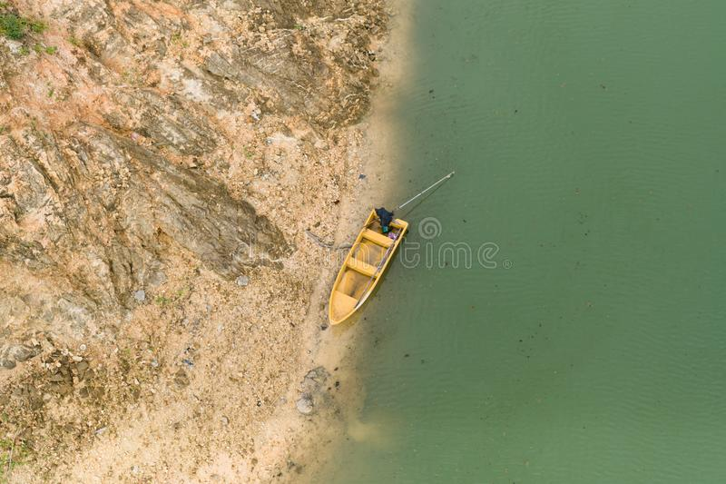 Den gula båten är parkerad på den gröna vattenstranden arkivbilder