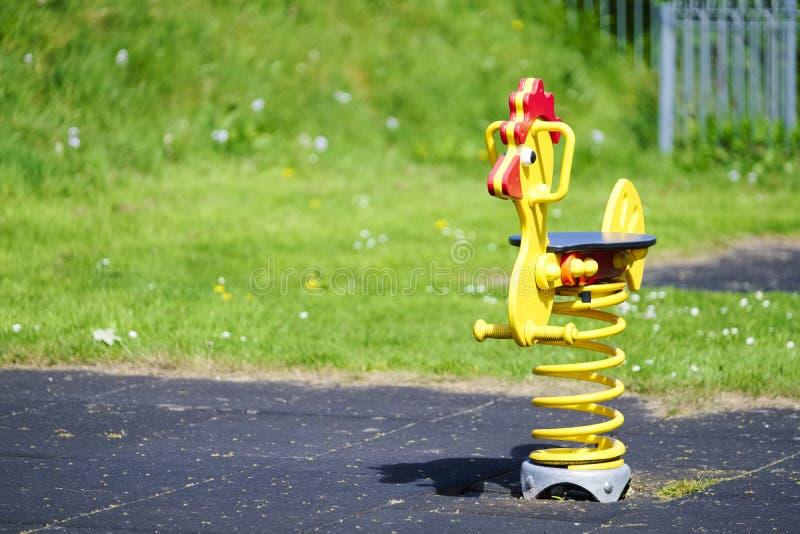 Den gula fega vårleksakritten på barns lek parkerar område royaltyfria bilder