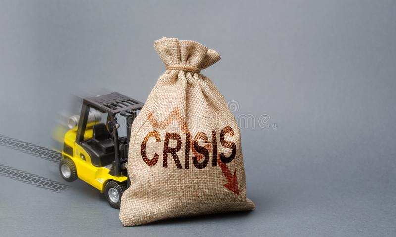 Den gula gaffeltrucken kan inte lyfta påsen med inskriftkrisen Ekonomisk kris, inaktivitet och nedgång av ekonomin royaltyfri foto