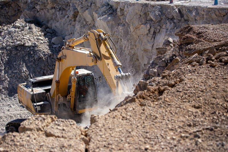 Den gula grävskopan fyller en dumper med vaggar på kolgruvor royaltyfri fotografi