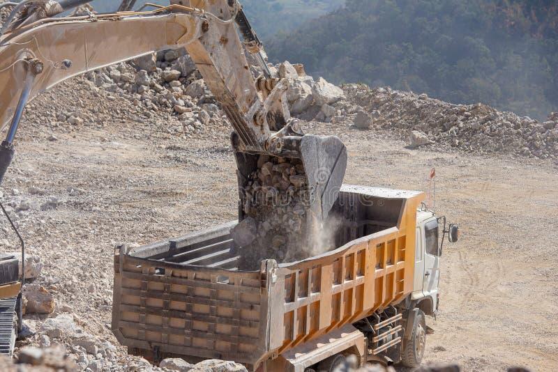 Den gula grävskopan fyller en dumper med vaggar på kolgruvor royaltyfria foton