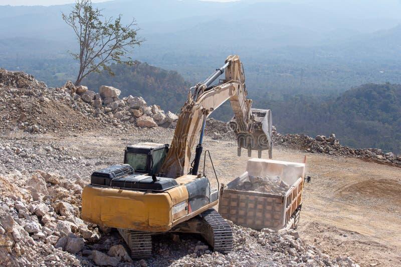 Den gula grävskopan fyller en dumper med vaggar på kolgruvor arkivfoto