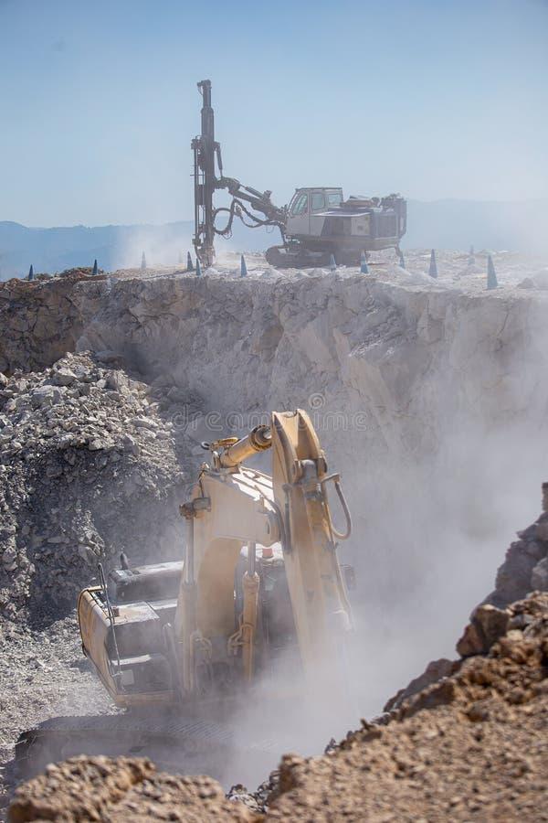 Den gula grävskopan fyller en dumper med vaggar på kolgruvor arkivbild