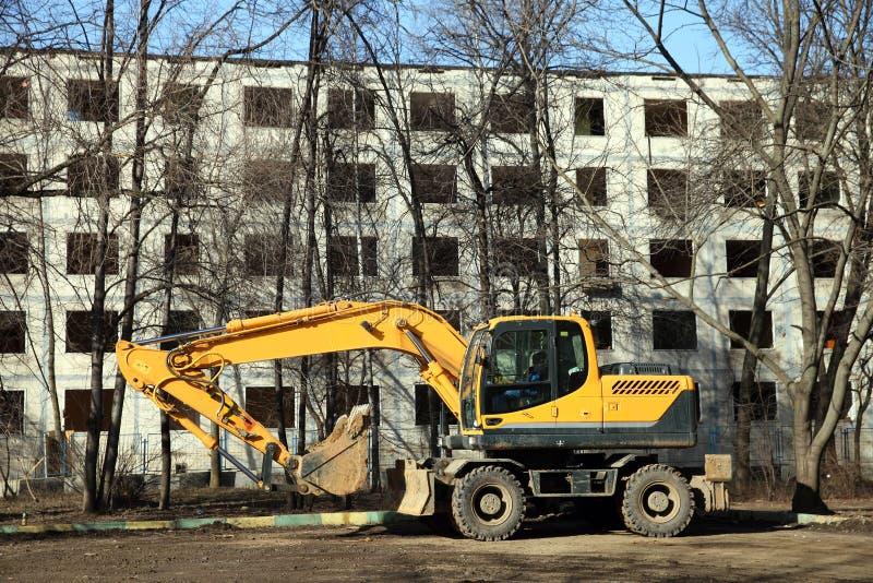 Den gula grävskopan på housebreaking arkivfoto