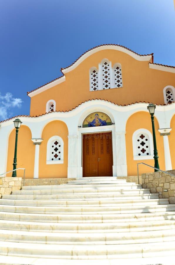 Den gula grekiska kyrkan med vit fönster och trappa arkivfoto