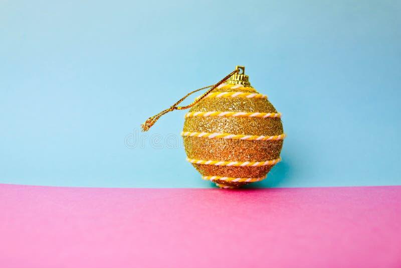 Den gula guld- bollen för jul för xmas för den lilla rundan festliga, julleksaken som över rappas, mousserar på en rosa purpurfär royaltyfria foton