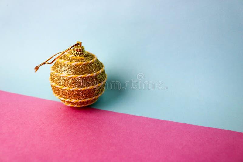 Den gula guld- bollen för jul för xmas för den lilla rundan festliga, julleksaken som över rappas, mousserar på en rosa purpurfär royaltyfri foto