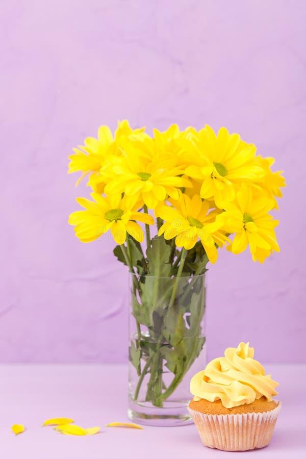 Den gula krysantemumet i exponeringsglas och muffin med guling lagar mat med grädde på violett pastellfärgad bakgrund Design för  royaltyfri foto