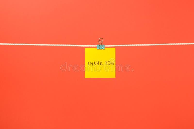 Den gula pappers- anmärkningen på klädstreck med text tackar dig arkivfoton