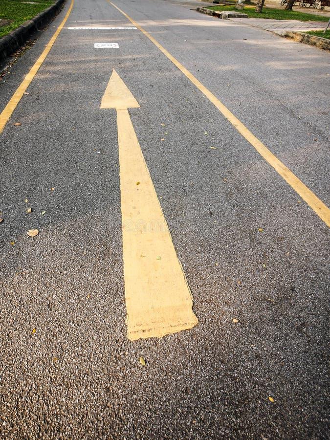 Den gula pilen på vägen arkivbilder