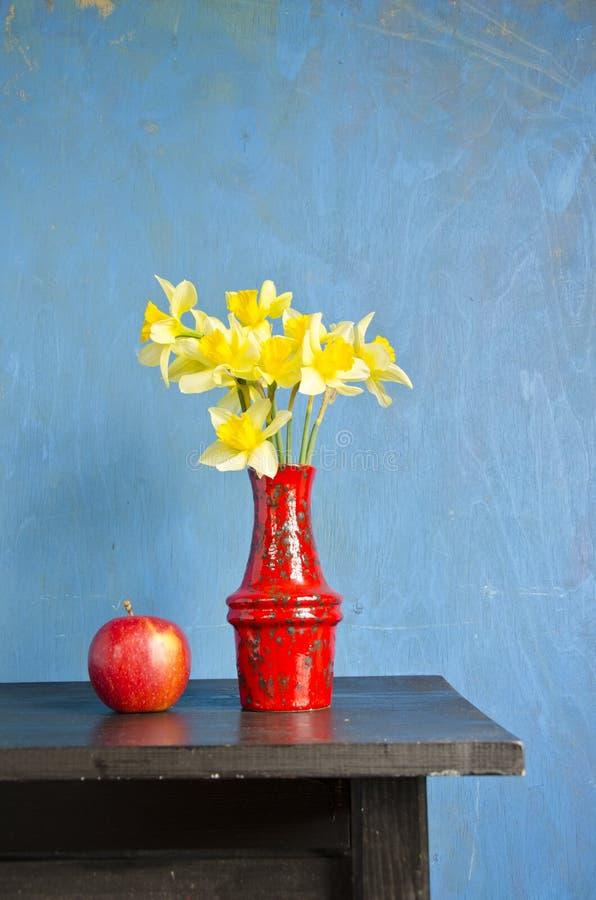 Gul pingstlilja i röd vase och äpple arkivfoto