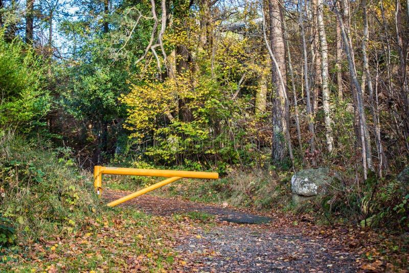 Den gula portbarriären förhindrar bilkörning på vandringsledet arkivfoton