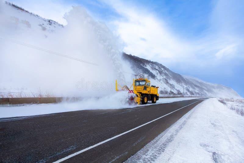 Den gula snöploglastbilen eller lastbilen för snöborttagning med snöplogbladet tar bort snön från huvudvägen efter förkylning fotografering för bildbyråer