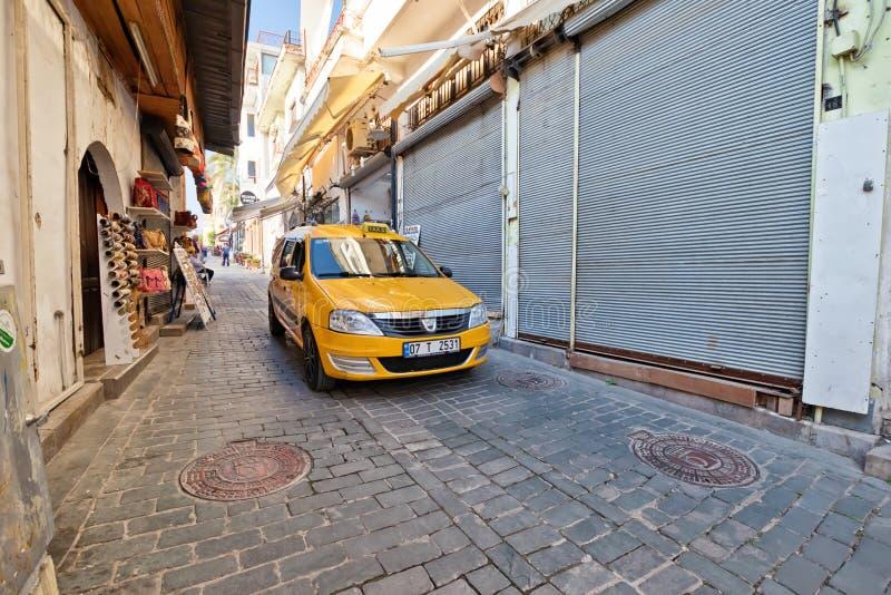 Den gula taxien rider på de bärande turisterna för vägen till lokalen tilldrar royaltyfria bilder