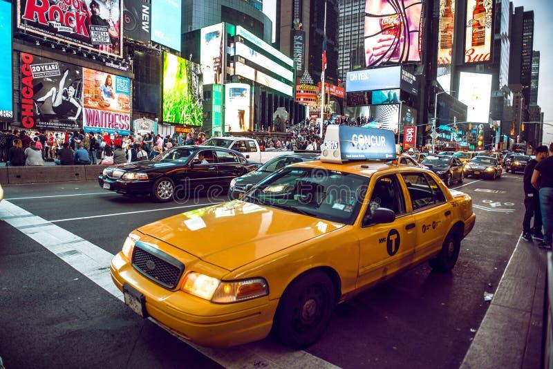 Den gula taxin på Times Squaretrafik och animerat LETT tecken, är ett symbol av New York City och Förenta staterna, Maj 12, 2016 arkivfoto
