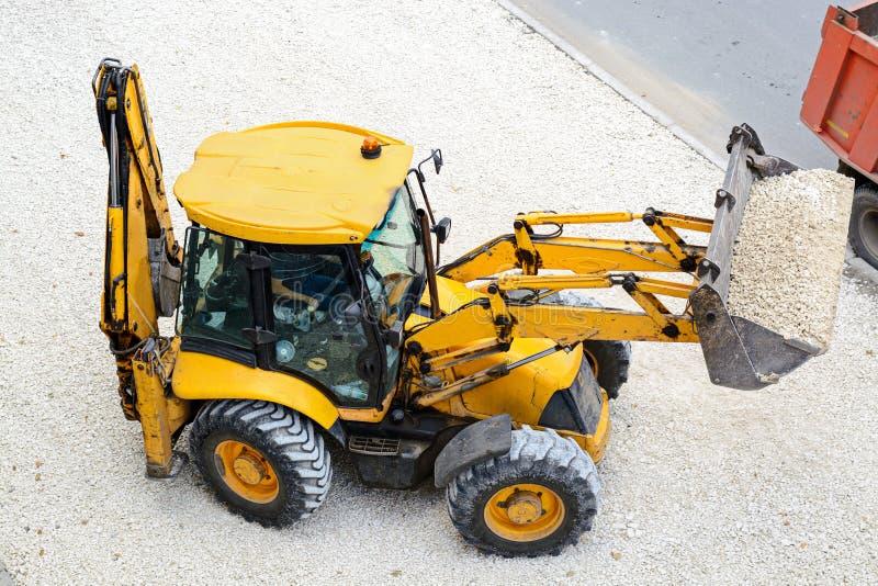 Den gula traktoren leder vägarbeten royaltyfria foton