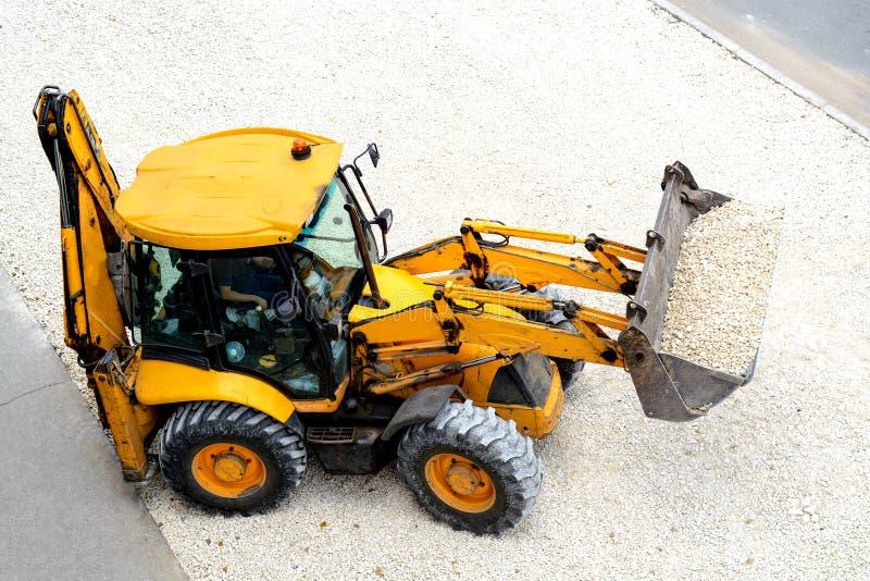 Den gula traktoren leder vägarbeten royaltyfri bild