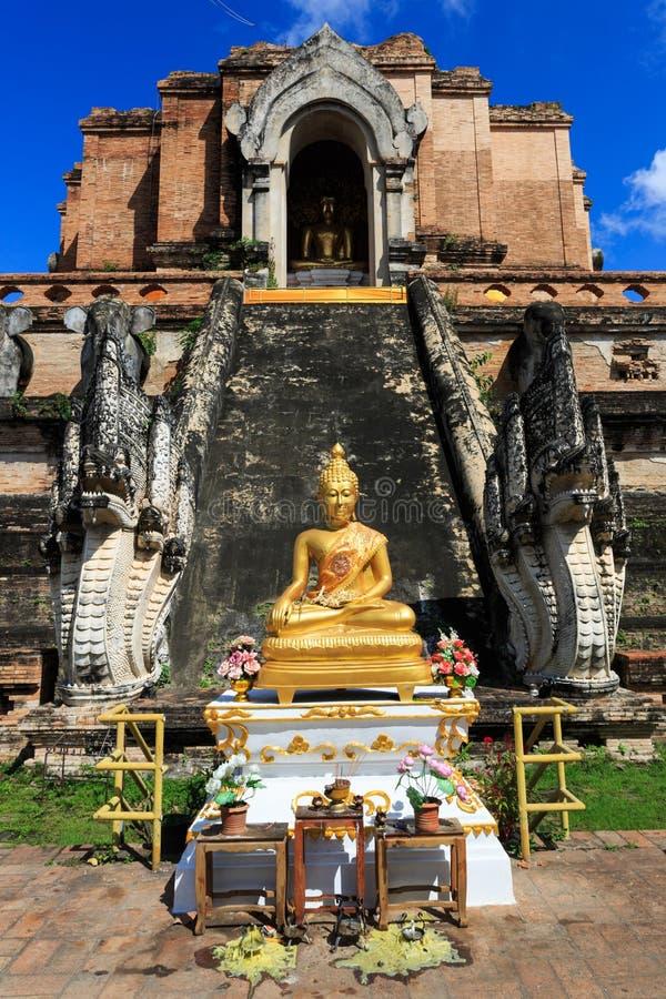 Den guld- Buddhastatyn framme av den brutna pagoden royaltyfri fotografi