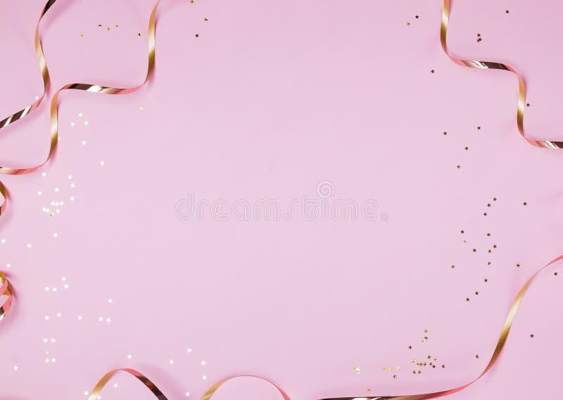 Den guld- dekorstjärnan formade konfettier och band som isolerades på pastellfärgad rosa bakgrund royaltyfri foto