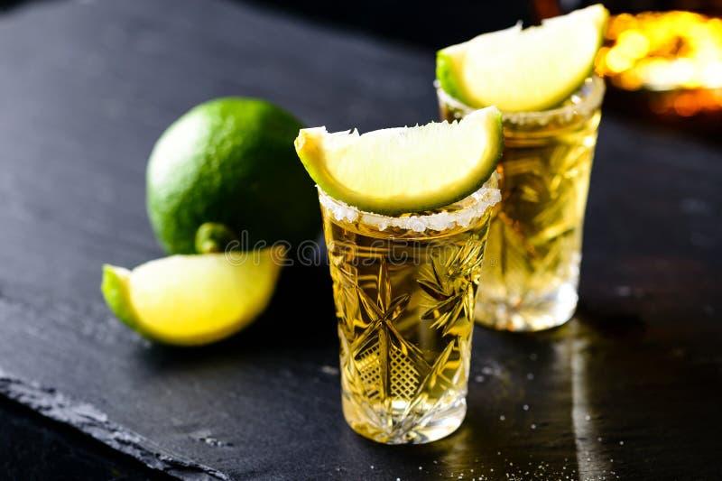 Den guld- mexicanska tequilaen med limefrukt och saltar royaltyfri foto