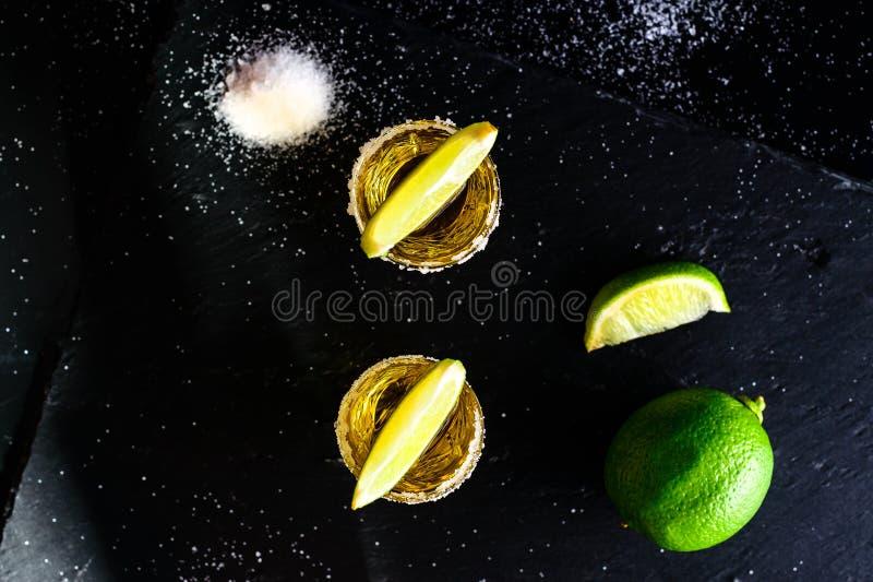 Den guld- mexicanska tequilaen med limefrukt och saltar på den mörka tabellen bästa sikt, royaltyfri foto